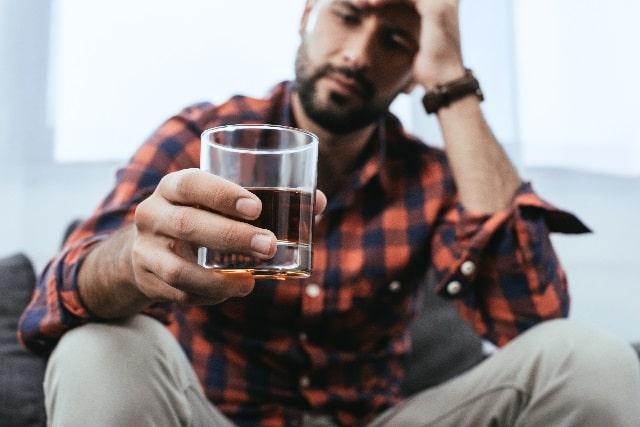 水の入ったコップを持ってなにかに悩む男性
