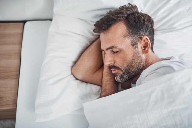 白い布団で横を向いて寝ている男性