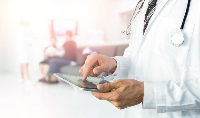 タブレットを指で操作する医師