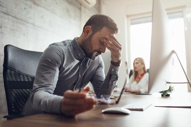 テーブルに座ってパソコンの前でおでこを抑える男性