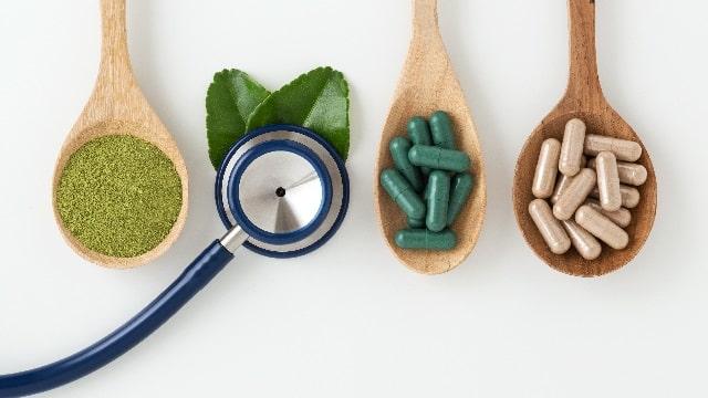 3つのスプーンと茶葉と聴診器とカプセルの薬と葉