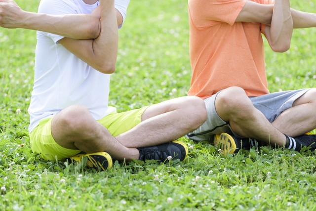 芝生でストレッチをするふたりの男性