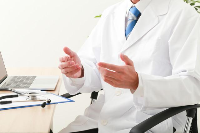 テーブルで手を広げてなにかを説明する男性医師