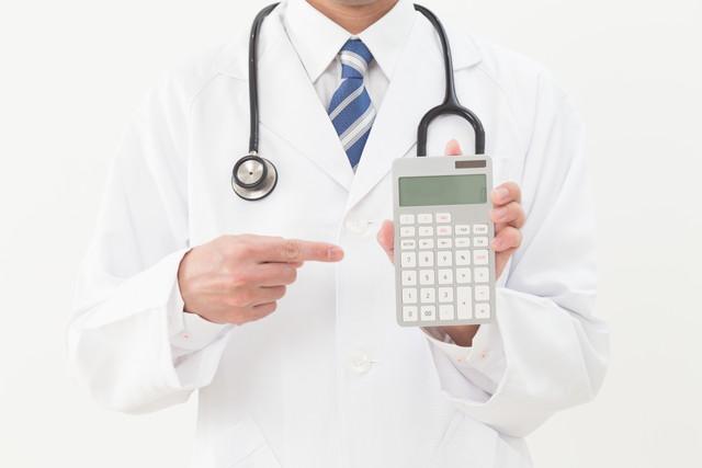電卓を指差す白衣の医者