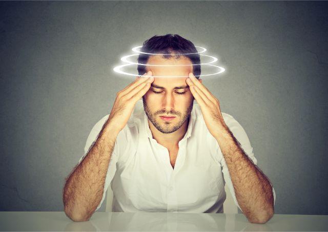 頭に光の輪をまといながら手でこめかみを押さえる男性