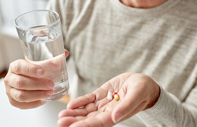 コップの水で薬をふたつぶ飲もうとするひと