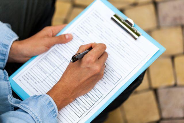 紙にペンで何かを書く男性の手