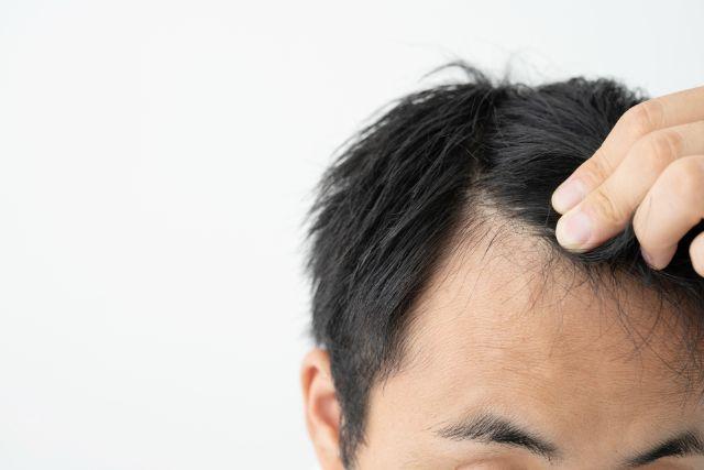 前髪を指でわける男性