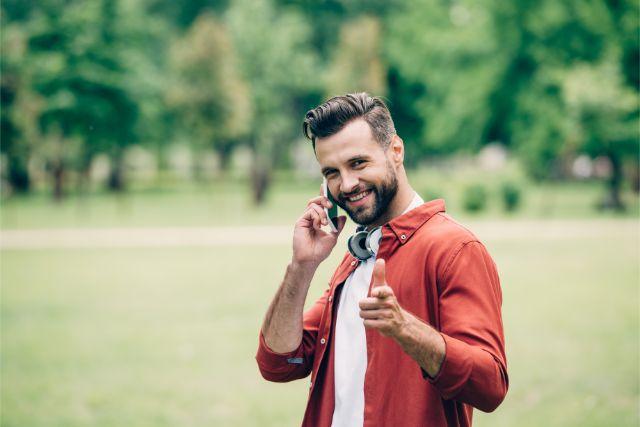 赤い服を着て携帯電話をかたてにこちらを指差している男性