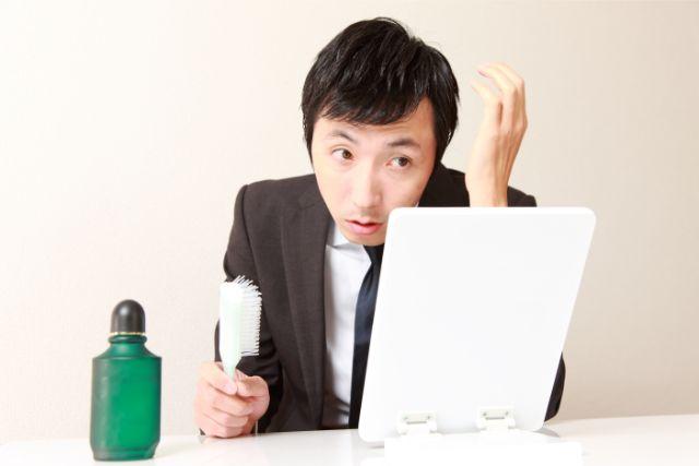 ブラシを手に育毛剤と鏡の前で頭皮を気にする男性