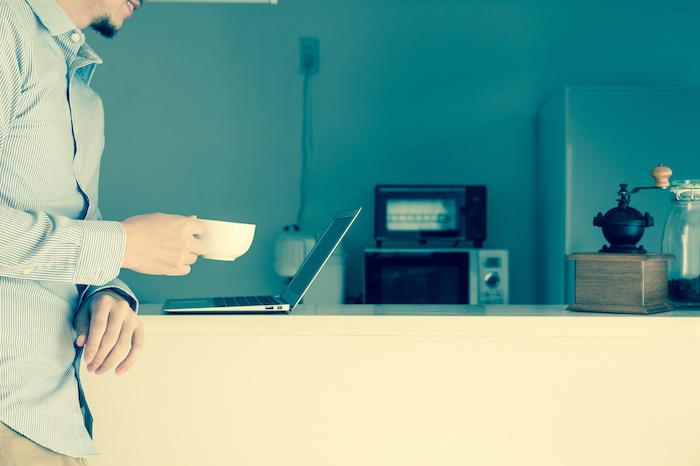 キッチンでコーヒーカップ片手にパソコンを見る男性
