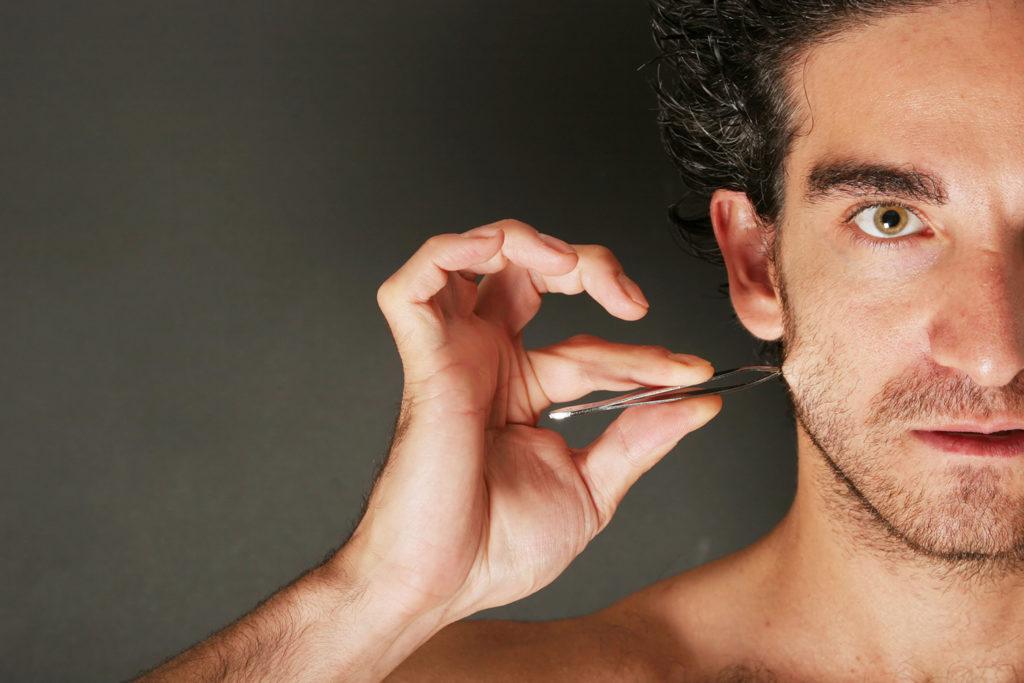 ピンセットで髭を抜こうとする男性