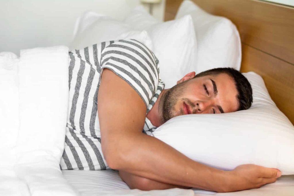 しましまのTシャツでベットに横たわる男性