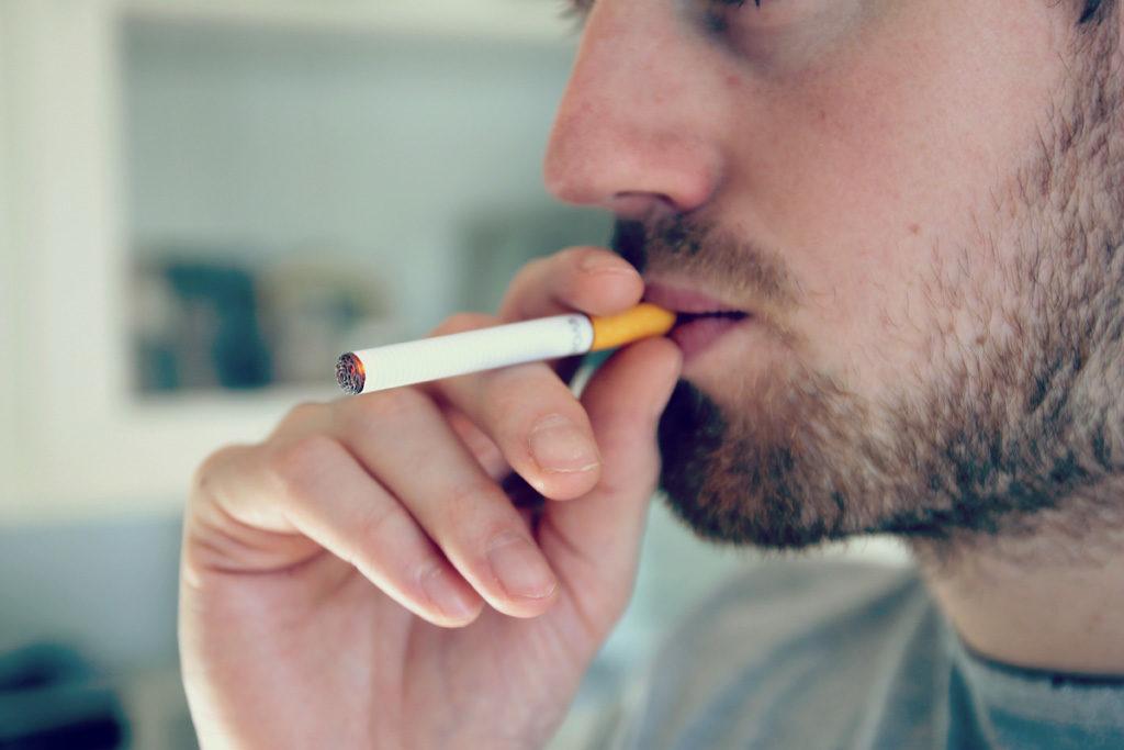 タバコに火を付けて加える男性
