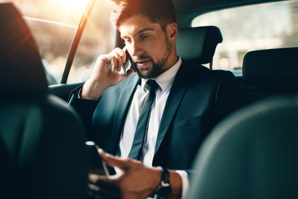 タクシーで電話をするヒゲの男性