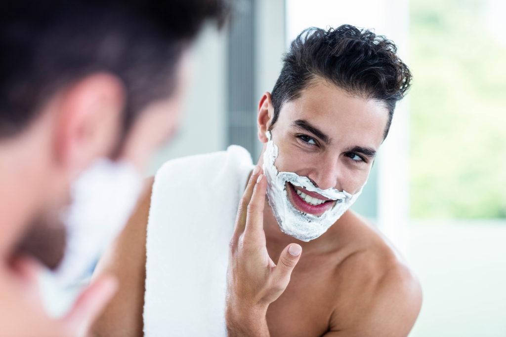あごに泡を付けて鏡ごしに微笑む男性