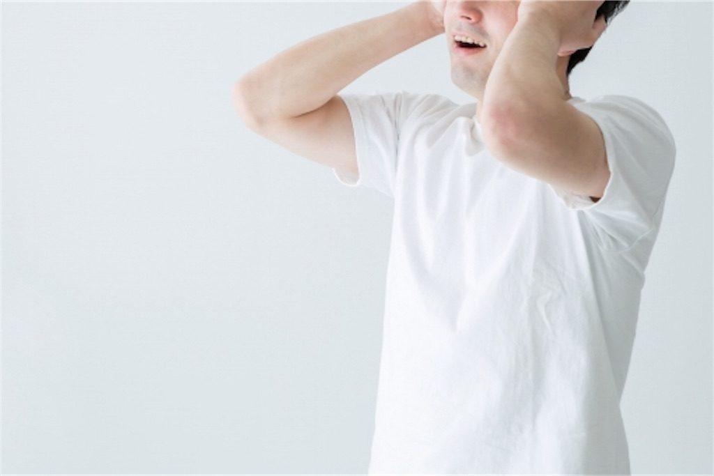 白いシャツの男性が頭を抱えている