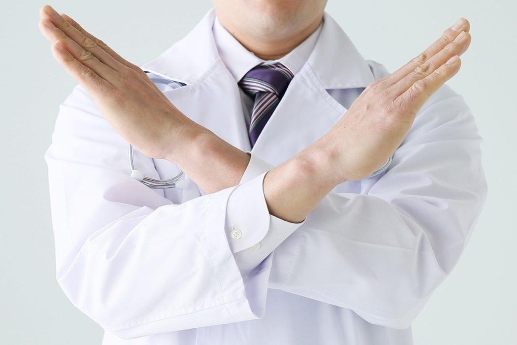 医者がこちらに向かって両手でバツサイン