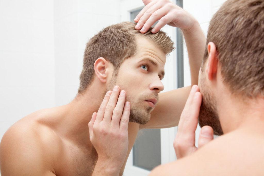 鏡に写った抜け毛を気にする男性
