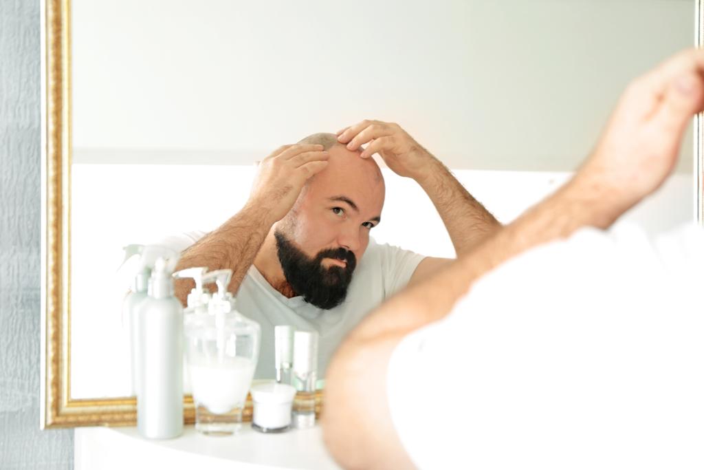 鏡の前で頭皮を触るあご髭の生えた男性