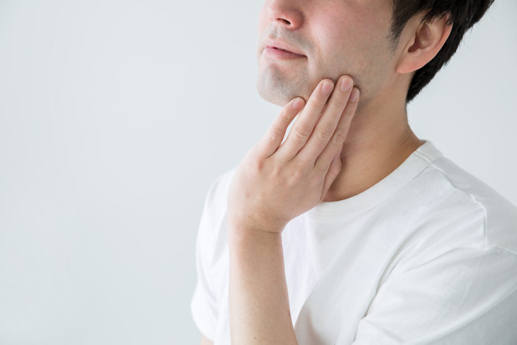 白いシャツで頬に手を当てている男性