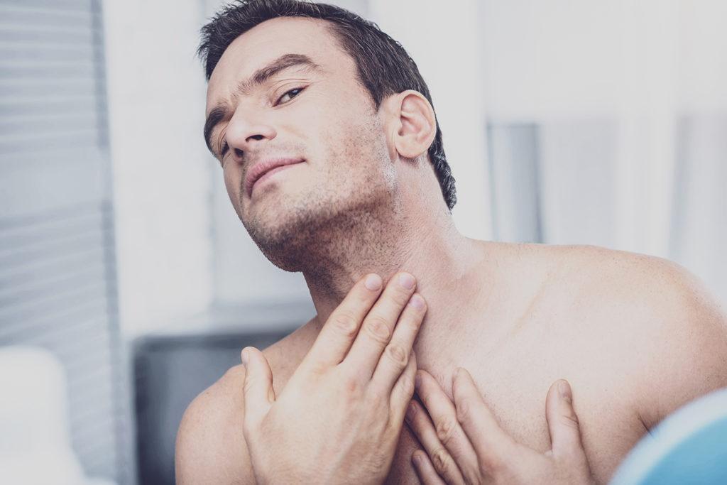 上半身裸で喉元を触っている男性