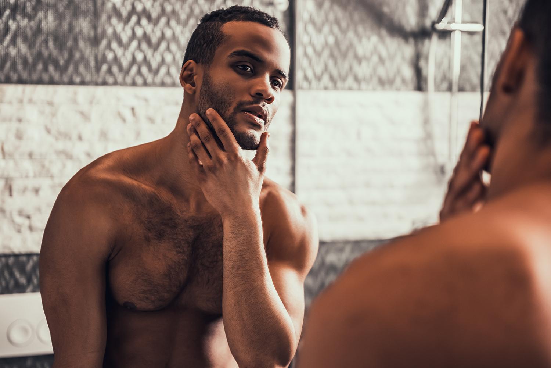 上半身ハダカで鏡の前で頬に手を当てている黒人男性
