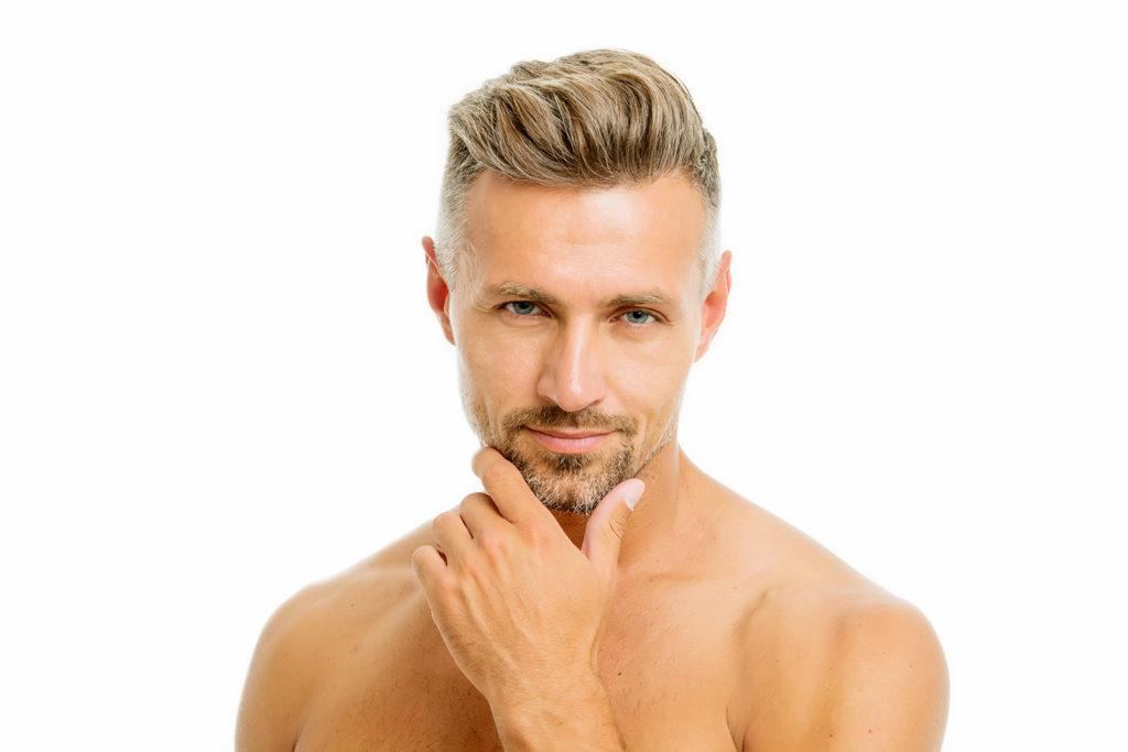 あご髭を触りながらこちらを見ている男性