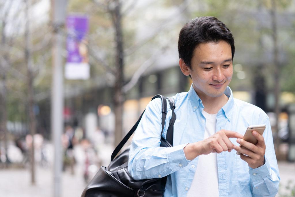 道で携帯を操作する男性