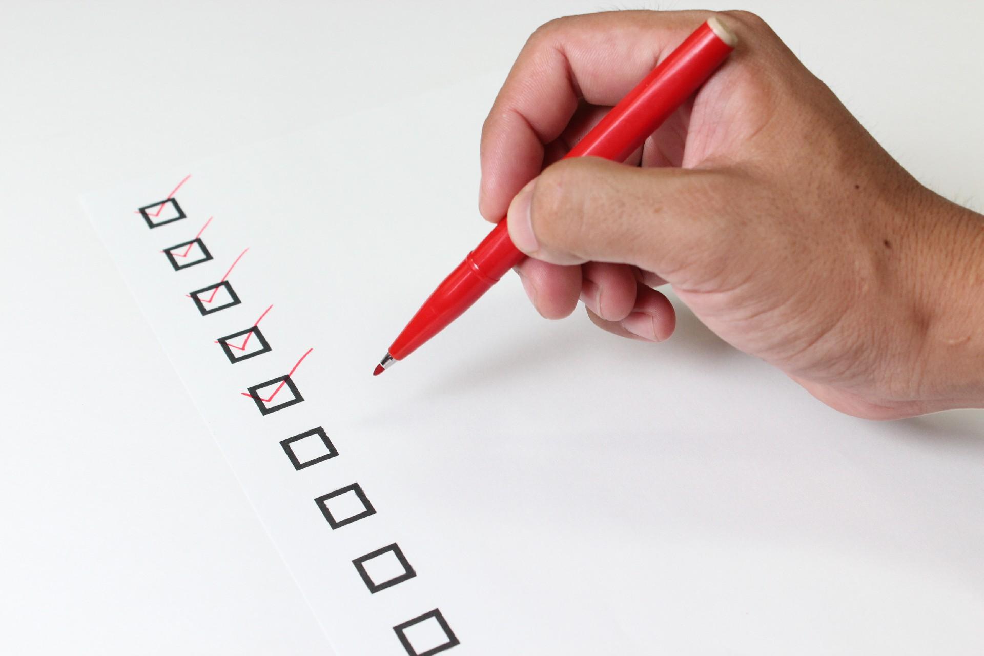 赤ペンでチェックサインを入れる手