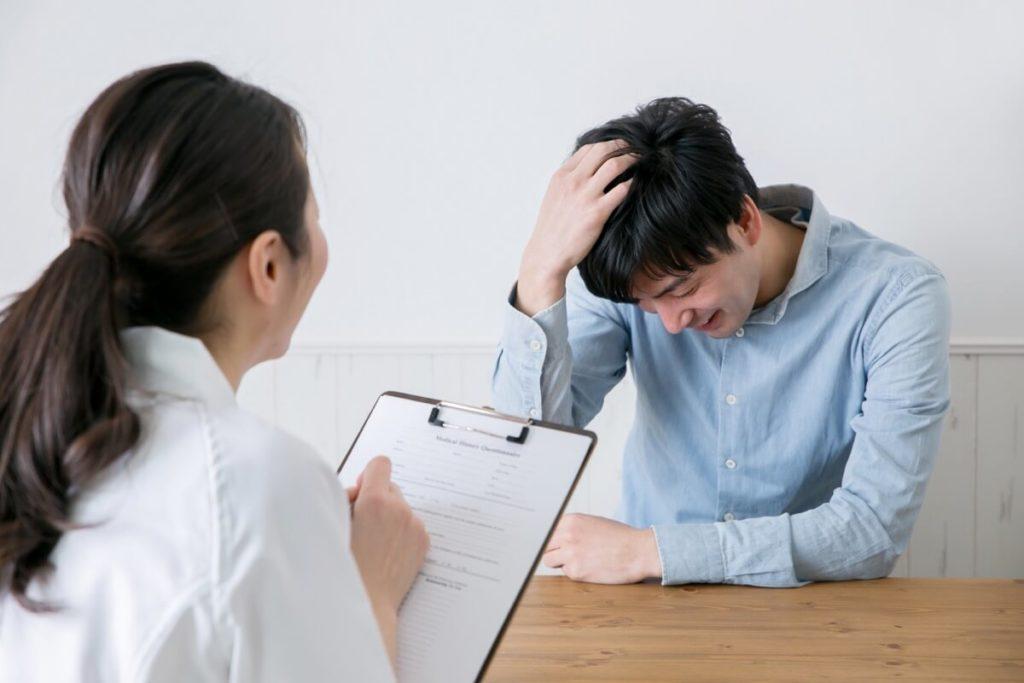 女性医師にカウンセリングを受け頭を気にする男性