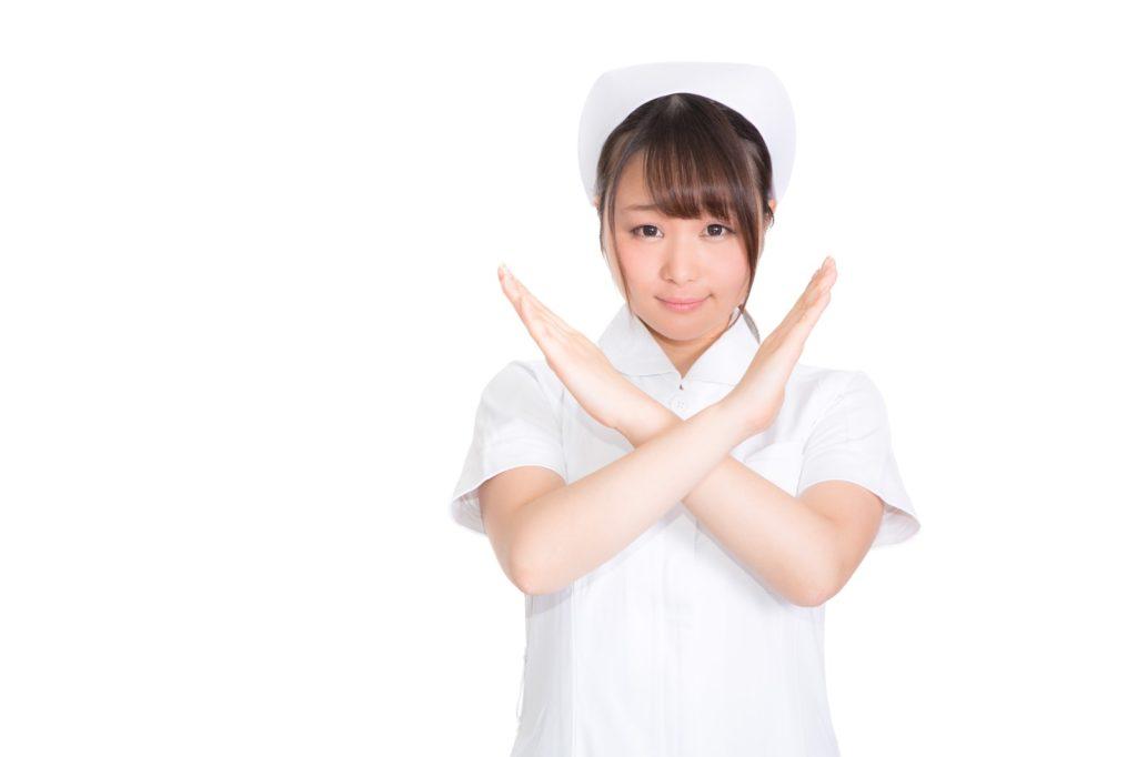 こちらを向いてバツサインをする看護師
