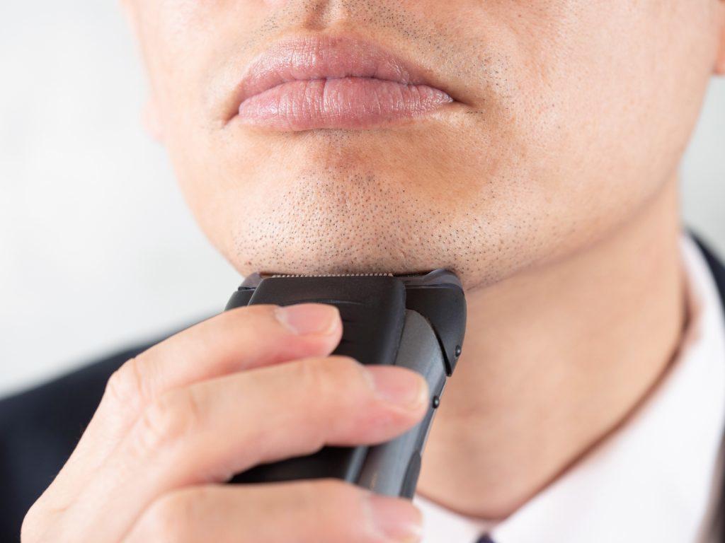 電気シェーバーで髭剃りをする男性