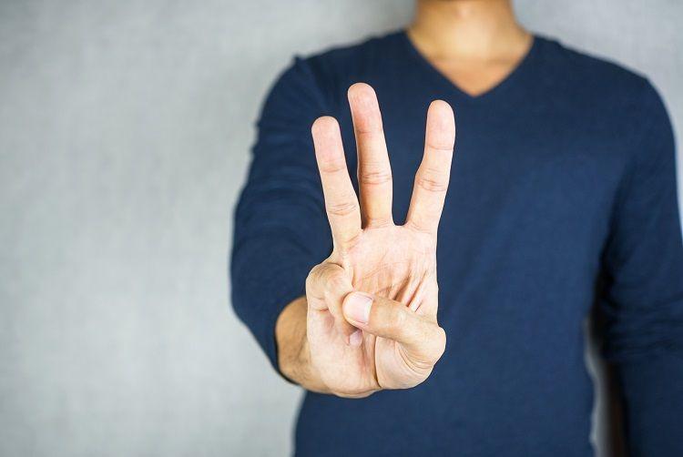 指を3本見せている男性