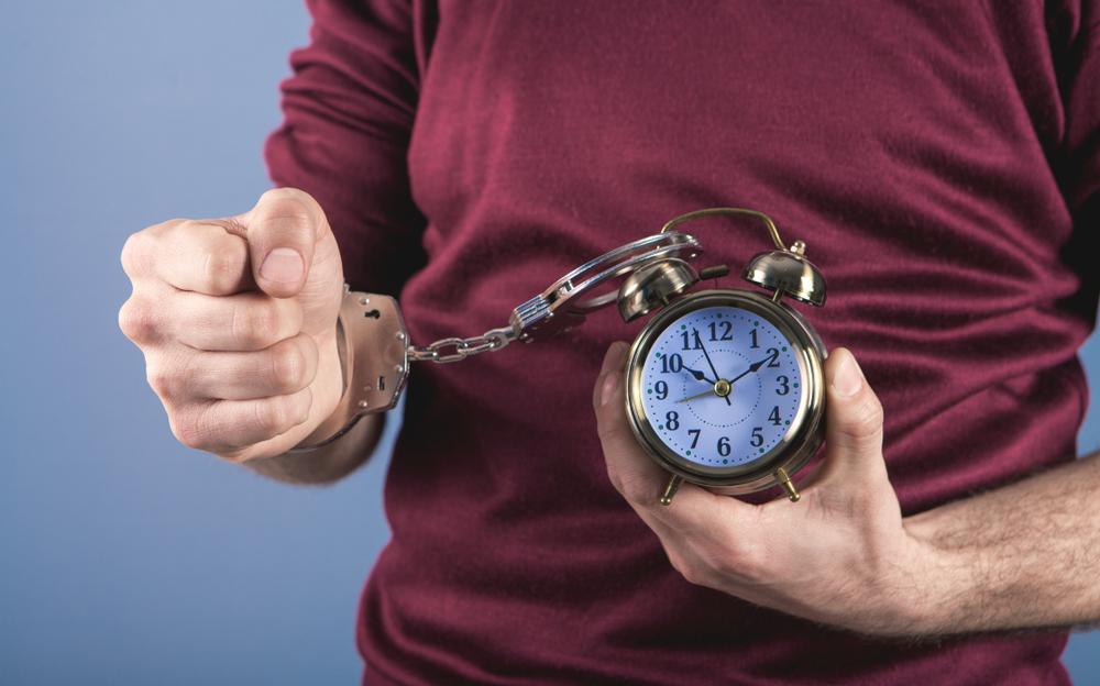 手首に手錠でつながっている時計