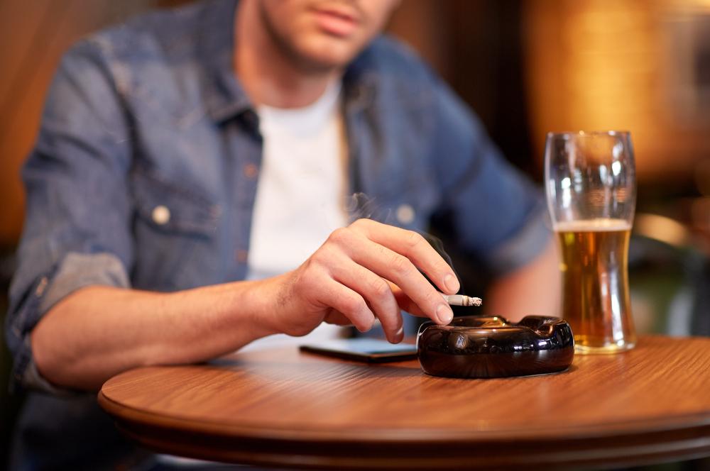 テーブルの上でビールとタバコを吸う男性