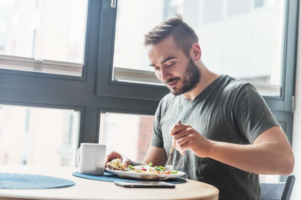 テーブルでランチプレートで食事する男性