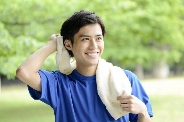運動してタオルで汗を拭く爽やかな男性