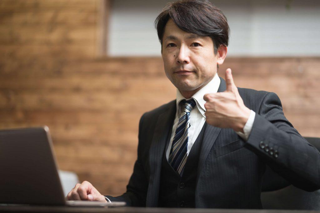 親指を立てるスーツの男性