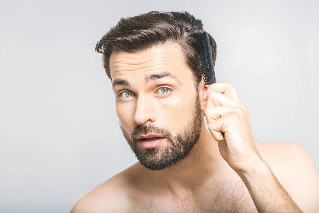 クシで髪をとかす男性