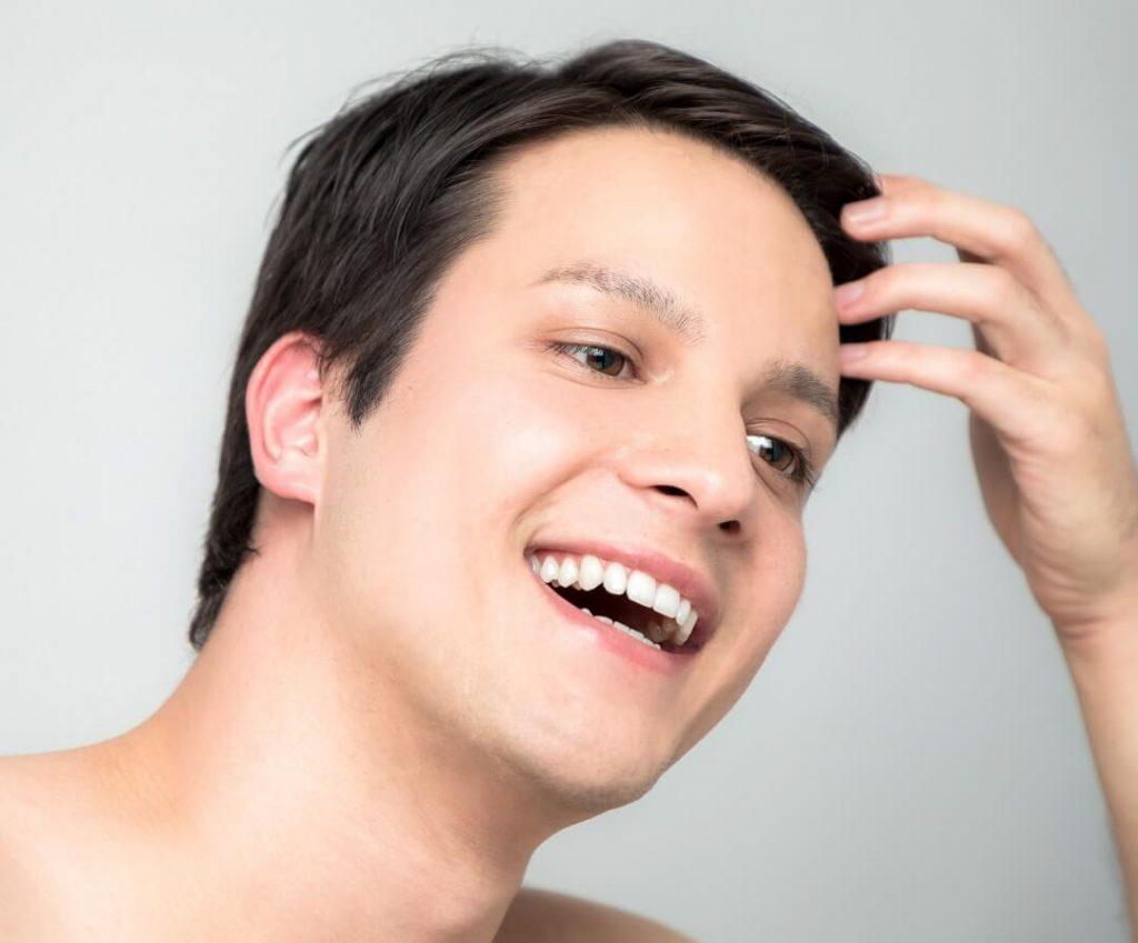 笑顔で頭を触る男性