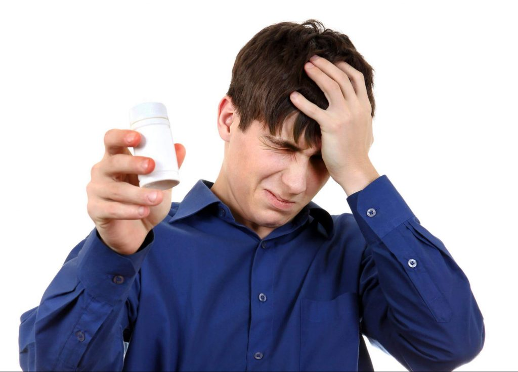 片手に薬を持って頭を抱える男性