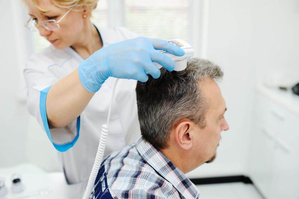 女性医師に頭皮の状態を見てもらう男性患者