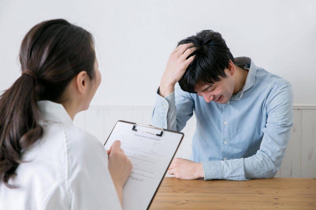 頭を触りながら女性医師のカウンセリングを受ける男性