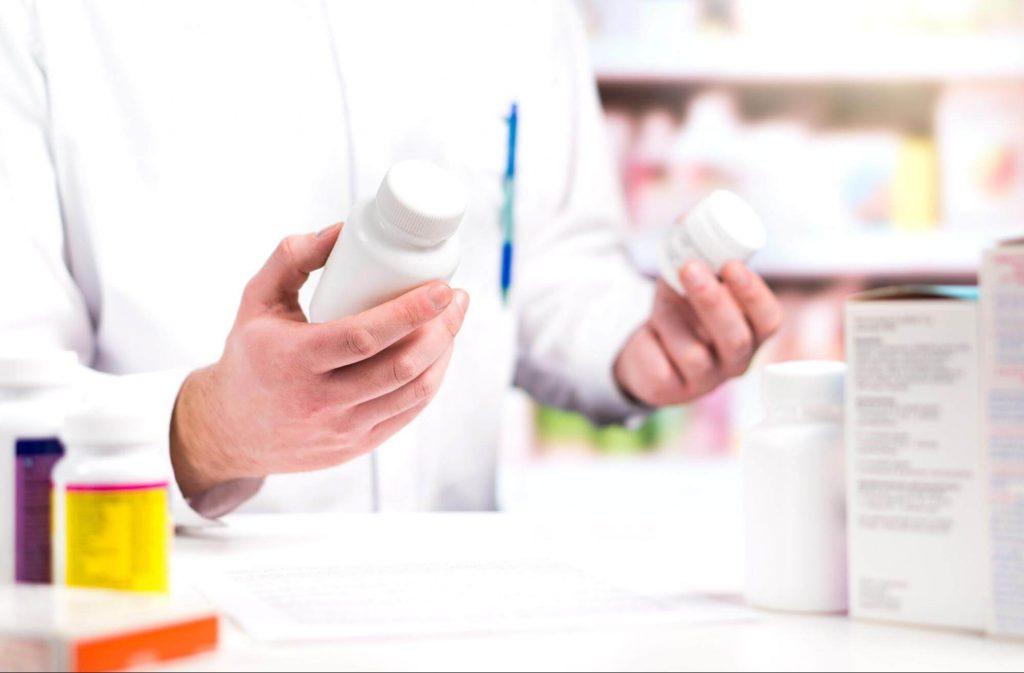 薬を手に持つ男性薬剤師
