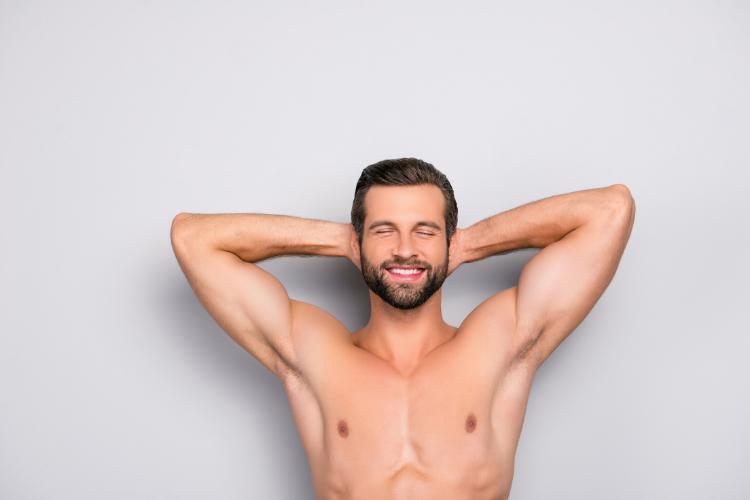 脇を広げて微笑んでいる裸の男性