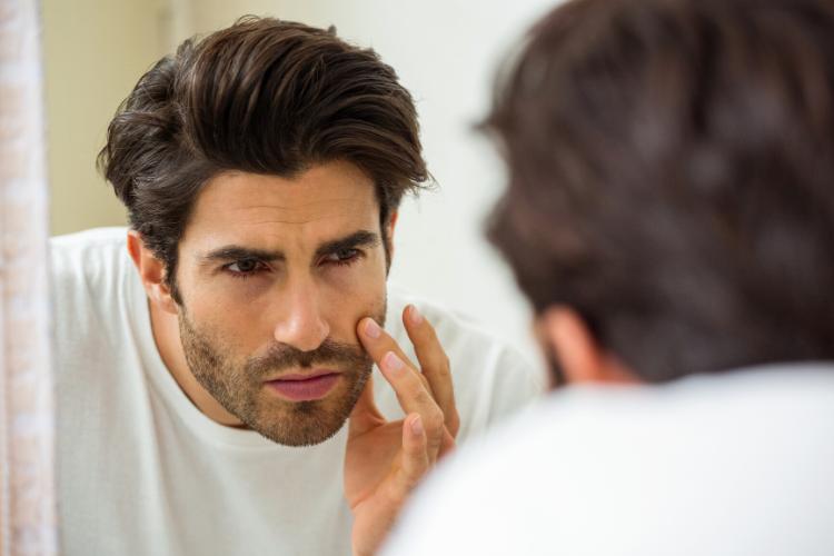 ヒゲが濃い男性が鏡を見ている