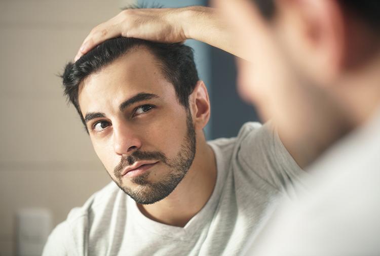髪を書き上げる男性