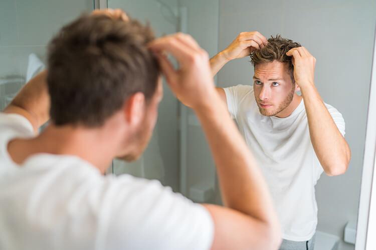 鏡ごしに頭を心配そうに見る男性
