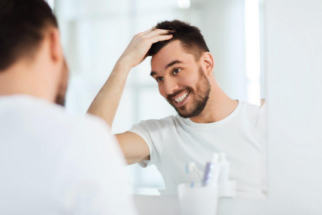 鏡を見て微笑んでいる男性